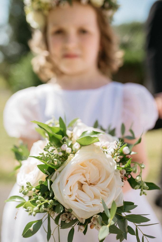 The flower girl is wearing Alix flower girl dress by Little Eglantine