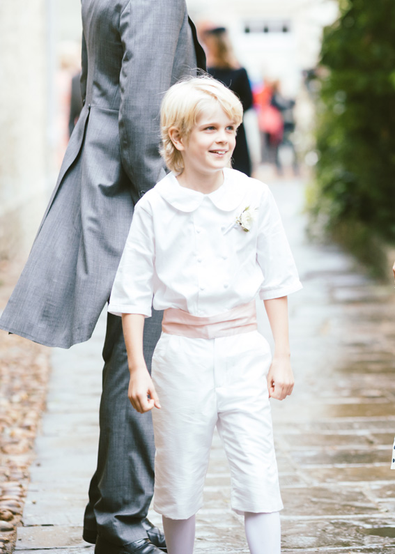Page boy at Camilla and Georges Blandford wedding wearing white page boy outfit with pink cummerbund by French Royal designer Little Eglantine
