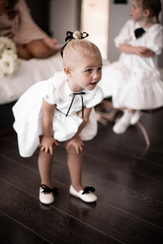 White flwoer girl dress with black satin ribbon with puff sleeves and peter pan collar by french designer little eglantine for megan cole wedding