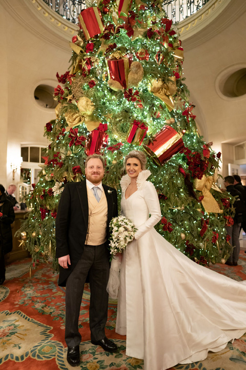 The bride and the groom at the Ritz, before the Christmas tree