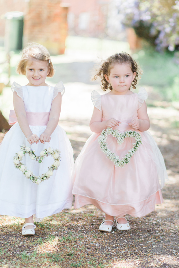 flower girls wearing designer dresses by Little Eglantine and floral hearts by Lavender Green Flowers